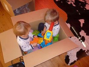 Kinder in Kiste samt Spielzeug